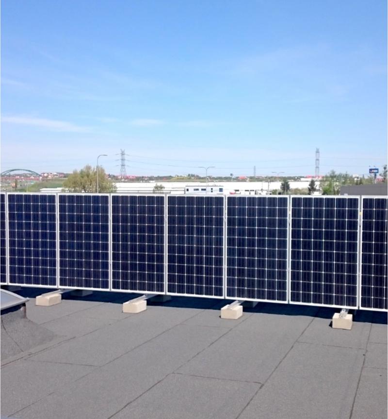 panele fotowoltaiczne zainstalowane pionowo na płaskim dachu